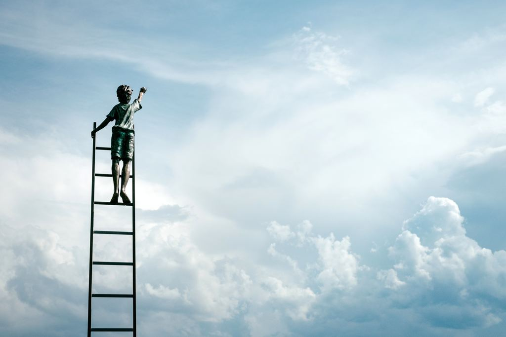 Person on ladder reaching for the clouds